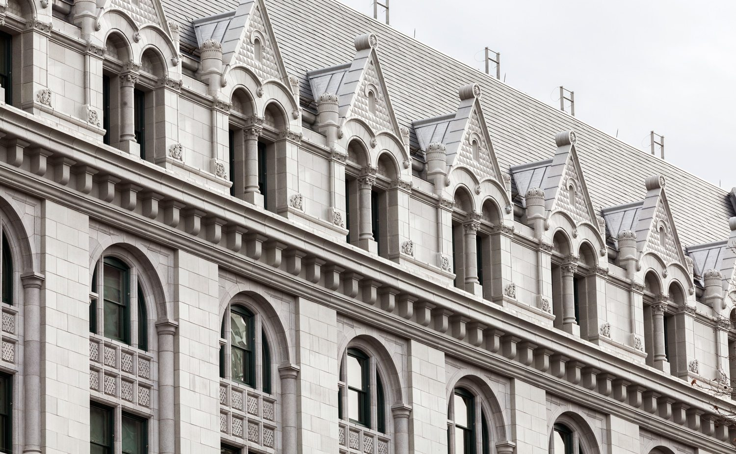 A detail shot of the upper portion and roof line of the Conrad B. Dubenstein U.S. Bankruptcy Courthouse in New York City. An award winning architectural terra cotta restoration utilizing hand press, RAM press and extrusion forming method to recreate over 17,000 terra cotta facade pieces.